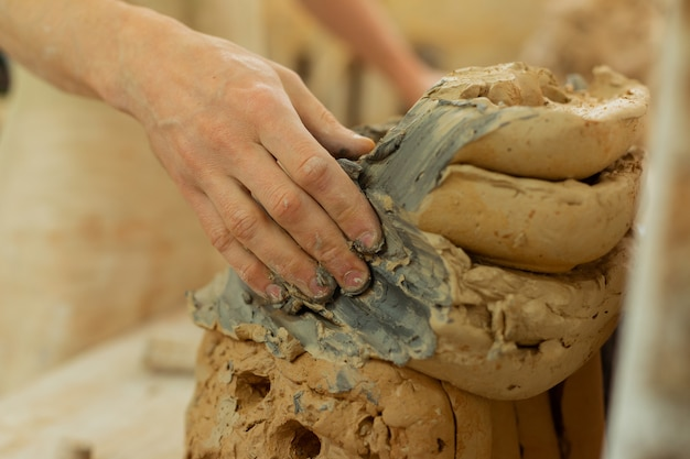 Zusätzliche materialien mitnehmen. starker tonmeister reibt seine finger in tonschlamm, während er mit der arbeit beginnt
