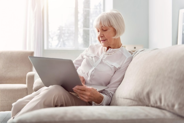 Zusätzliches einkommen. charmante ältere frau, die auf der couch sitzt und an ihrem laptop arbeitet und nach einigen tipps sucht