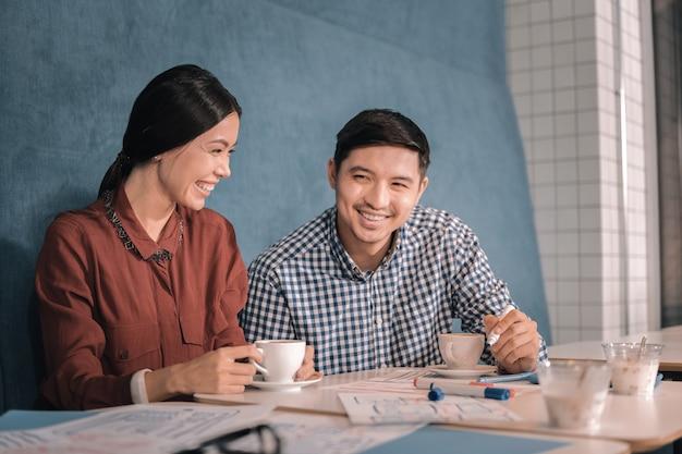 Zusammen arbeiten. draufsicht auf intelligente kreative freiberufler, die zusammenarbeiten und in der cafeteria sitzen