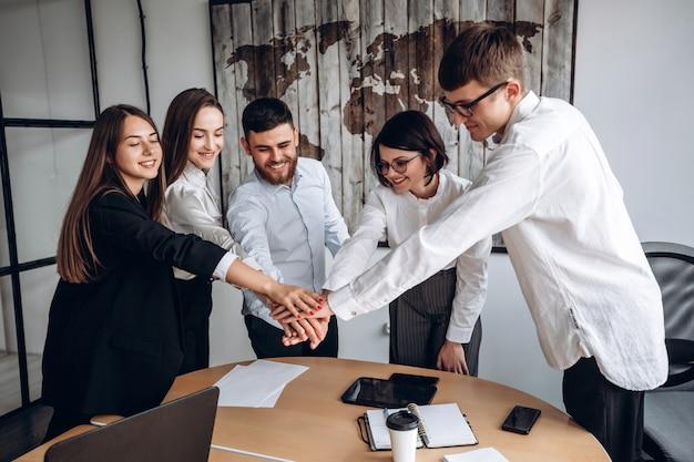 Zusammen arbeiten. ein freundliches team von geschäftsleuten, die ihre hände zusammenlegen, ist eins.