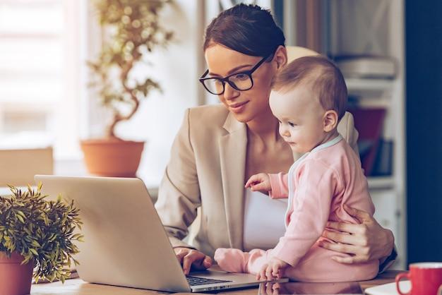 Zusammen arbeiten. junge schöne geschäftsfrau mit laptop beim sitzen mit ihrem baby an ihrem arbeitsplatz
