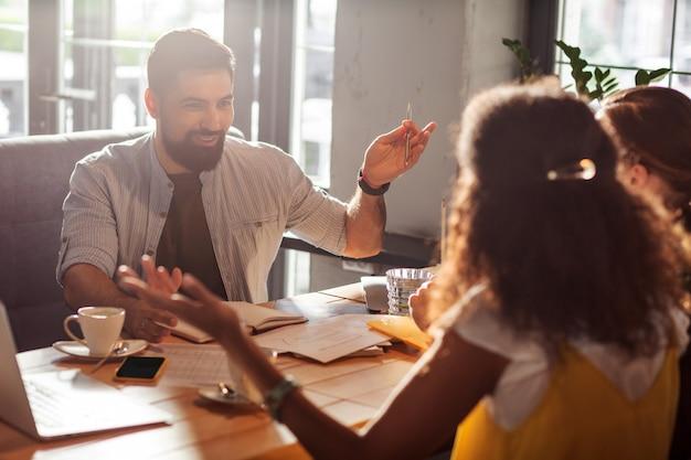 Zusammen arbeiten. positiver fröhlicher mann, der beim sprechen mit seinem team lächelt