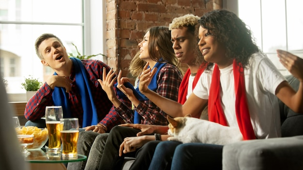 Zusammen. aufgeregte leute, die sportmatch, meisterschaft zu hause beobachten. multiethnische gruppe von freunden, fans, die ihre lieblingssportmannschaft anfeuern