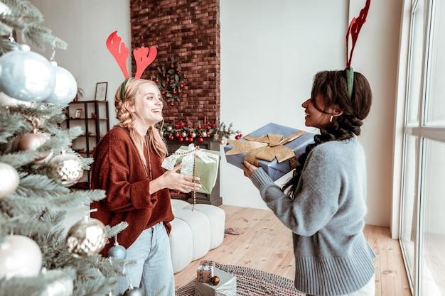 Zusammen herumalbern. freudige langhaarige damen, die feiertagselemente tragen und sich gegenseitig verpackte geschenke weihnachtskonzept präsentieren