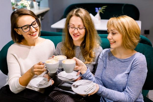 Zusammen kaffee trinken. draufsicht von den baumschönheiten, die tasse kaffees in den händen und im lächeln halten. frauen im café drinnen. treffen der besten freunde. kaffee mit kuchen