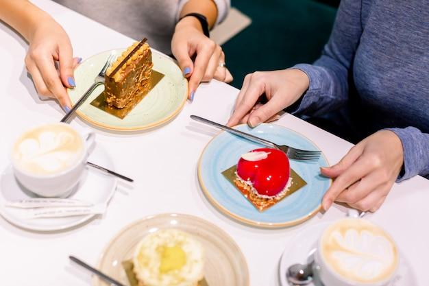 Zusammen kaffee trinken und desserts essen. draufsicht von händen von zwei schönheiten, die hände auf platten mit köstlichen nachtischen im café halten. treffen der besten freundin. kaffee mit kuchen