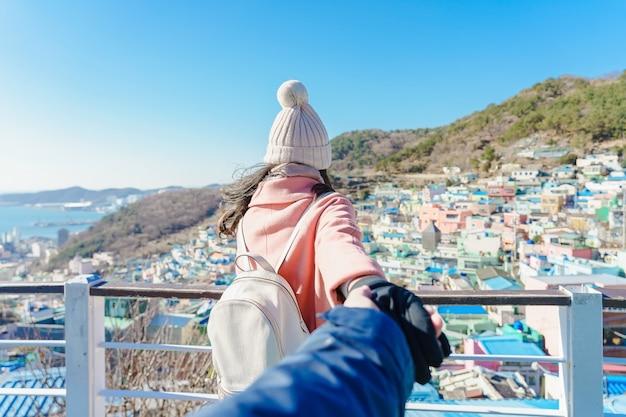 Zusammen reisen. folge mir, junge frau, die ihren freund zum kulturdorf gamcheon in busan, südkorea, führt