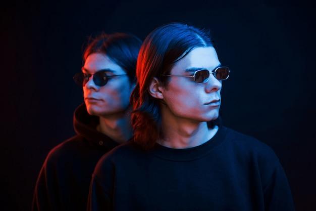 Zusammen stehen wir. porträt von zwillingsbrüdern. studioaufnahme im dunklen studio mit neonlicht