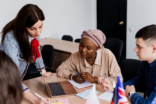 Zusammenarbeit. arbeiten in einer multiethnischen gruppe von studenten. lehrer lernen gemeinsam fremdsprachen im unterricht.