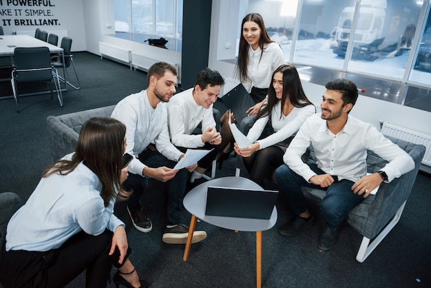 Zusammenarbeit in freundlicher atmosphäre in der nähe eines tisches mit einem silberfarbenen laptop