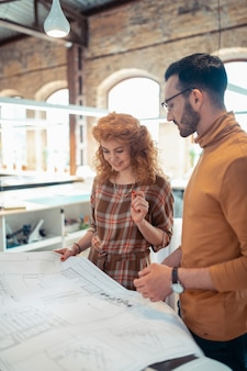Zusammenarbeit mit kollegen. lockige schöne frau, die sich bei der zusammenarbeit mit kollegen gut fühlt