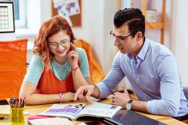 Zusammenarbeit und partnerschaft. fröhliche gutaussehende menschen, die das buch beim gemeinsamen lernen lesen