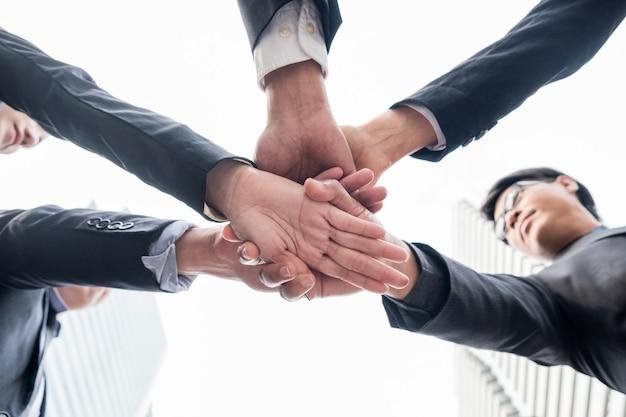 Zusammenarbeit von geschäftsteams, die einheit mit ihren gestapelten händen zeigen