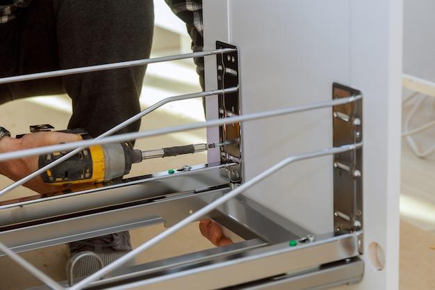 Zusammenbau von möbeln holzarbeiter schrauben mit einem akkuschrauber schubladen mülltonne in der küche
