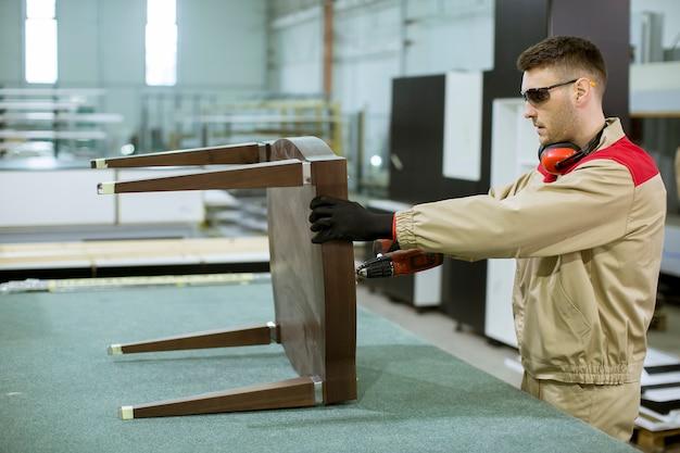 Zusammenbauende möbel des jungen arbeitnehmers in der fabrik