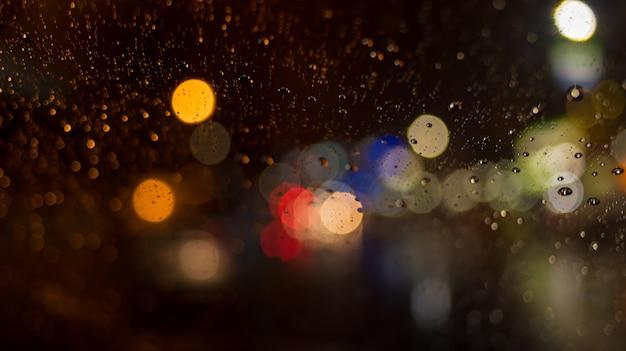 Zusammenfassung defocused des regens fällt auf autoglas- und bokehhintergrund