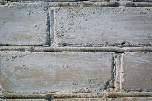 Zusammenfassung verwitterte beschaffenheit befleckte den alten stuck hellgrauen und gealterten weißen backsteinmauerhintergrund der farbe