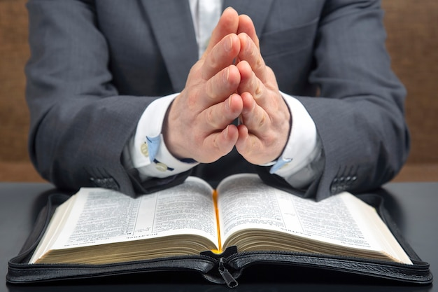 Zusammengefaltete männliche hände liegen auf einer offenen heiligen bibel in nahaufnahme