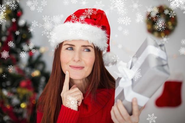 Zusammengesetztes bild der festlichen rothaarigen, die weihnachtsgeschenk hält