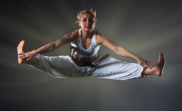 Zusammengesetztes bild des karate-mädchens, das auf dunklem hintergrund springt