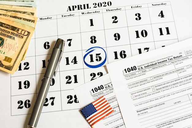 Zusammensetzung am tag der steuerzahlung im april mit banknoten und steuerformular.