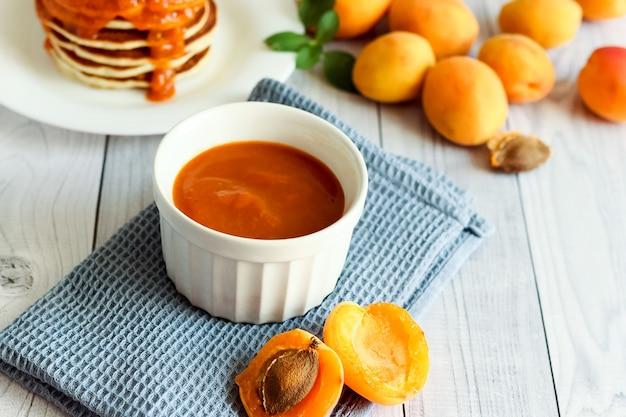 Zusammensetzung aprikosenmarmelade auf weißem holz