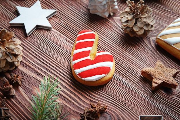 Zusammensetzung aus leckerem keks und weihnachtsdekor auf holztisch, nahaufnahme