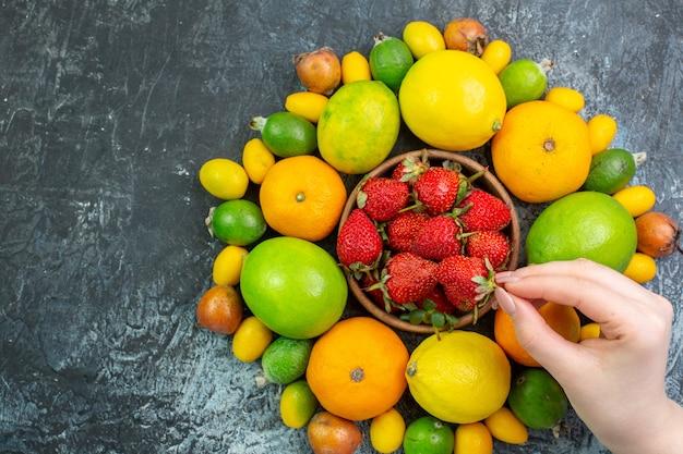 Zusammensetzung der frischen früchte von oben mit roten erdbeeren auf dem grauen hintergrund