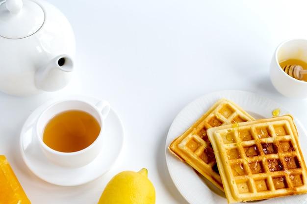 Zusammensetzung der frühstücksprodukte. waffeln, tee und zitrone. weißer hintergrund