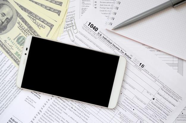 Zusammensetzung der gegenstände, die auf dem steuerformular 1040 liegen. dollarscheine, stift, smartphone, büroklammer und notizblock. reinigen sie den schwarzen bildschirm für die textplatzierung