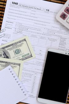 Zusammensetzung der gegenstände, die auf dem steuerformular 1040 liegen. dollarscheine, taschenrechner, smartphone, büroklammer und notizblock