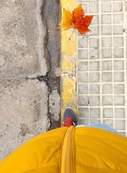 Zusammensetzung der herbstfarben mit einem blatt und einer person, die rote und orangefarbene farben kleidet