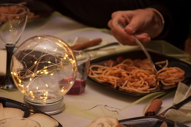 Zusammensetzung der led-dekoration an einem tisch eines typisch italienischen restaurants während eines weihnachtsessens. im hintergrund ein teller spaghetti.
