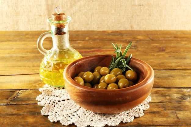Zusammensetzung der runden schüssel mit grünen oliven in der nähe von ölkanne auf spitzendeckchen, auf rustikalem holztisch, auf sackleinenraum