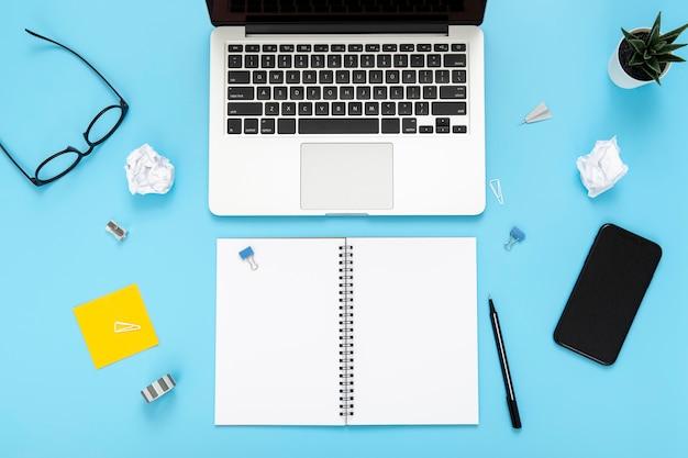Zusammensetzung der schreibtischelemente auf blauem hintergrund mit leerem notizbuch