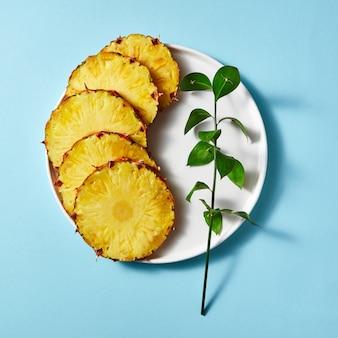 Zusammensetzung der stücke der reifen ananas und eines grünen zweigs in einem teller auf einem dunklen papierhintergrund, draufsicht