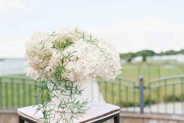 Zusammensetzung der weißen hortensien in der hochzeitsdekoration der ausgangszeremonie