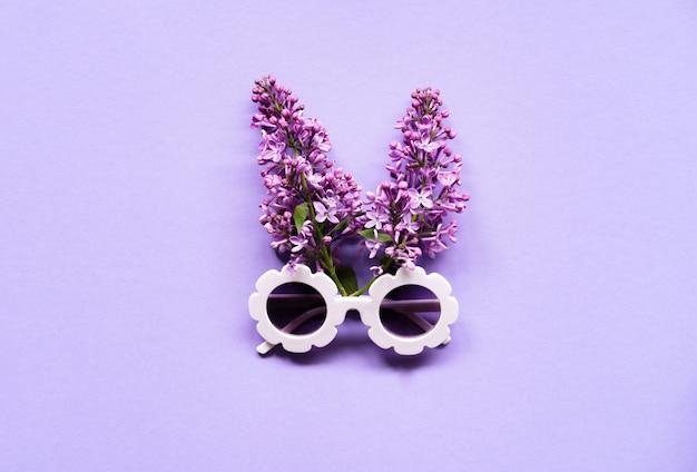 Zusammensetzung der weißen modernen sonnenbrille mit lila blumen. sommer kreatives konzept. flache lage. ansicht von oben