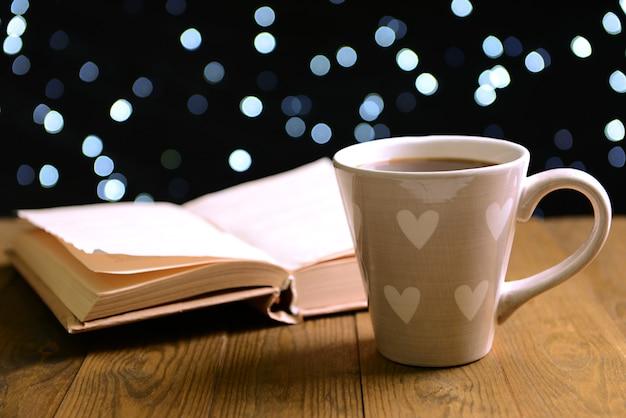 Zusammensetzung des buches mit tasse kaffee auf dem tisch