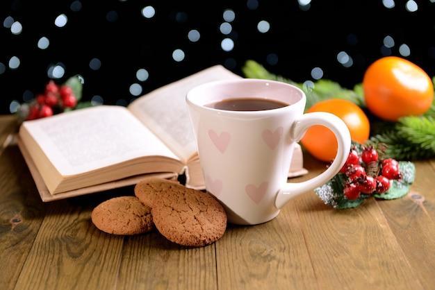 Zusammensetzung des buches mit tasse kaffee und weihnachtsdekorationen auf dem tisch auf dunklem hintergrund