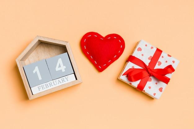 Zusammensetzung des hölzernen kalenders, der weißen geschenkboxen des feiertags und der roten textilherzen auf buntem. der vierzehnte februar. valentinstag