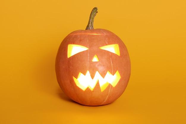 Zusammensetzung des leuchtenden lichts von innen jack o laterne, kürbis isoalted auf gelb, feiertag feiern, letzte oktober nacht, orange kürbis auf studiowand. halloween-konzept.