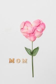 Zusammensetzung des muttertitels nahe rosa blüte in der form des herzens