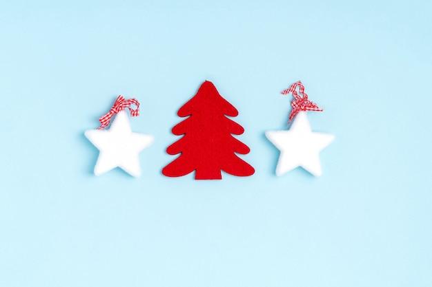 Zusammensetzung des neuen jahres und des weihnachten von den weißen sternen, chrismas baum auf blauem pastellpapier. draufsicht, flache lage, copyspace
