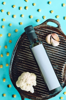 Zusammensetzung des olivenöls in der flasche auf dem grill mit knoblauch und maiskörnern. pastellblau