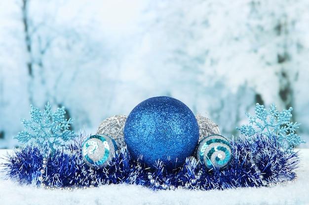 Zusammensetzung des weihnachtsschmucks auf heller winteroberfläche