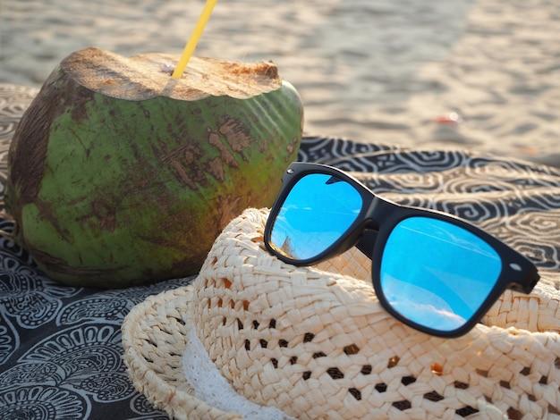 Zusammensetzung einer sonnenbrille, die auf dem panama liegt und einer kokosnuss mit einer röhre im hintergrund. sandstrand dahinter. urlaubskonzept