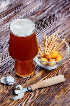 Zusammensetzung eines glases bieres mit schaum auf einem rustikalen holztisch