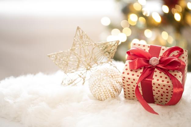 Zusammensetzung eines weihnachtsgeschenks und der neujahrsdekoration auf einem hellen hintergrund mit gerlandenlichtern.