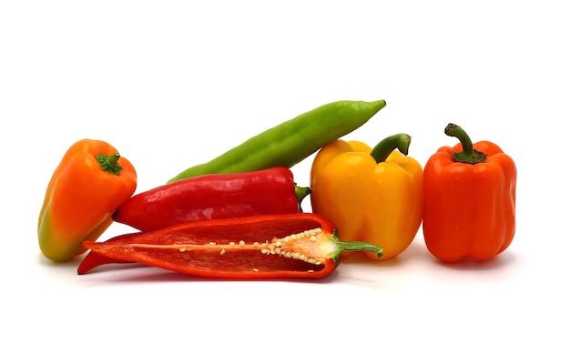Zusammensetzung mehrerer paprika und ihrer hälften verschiedener farben auf hellem hintergrund. natürliches produkt. natürliche farbe. nahansicht.